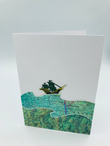 A handmade card featuring a green galleon on a wavy sea
