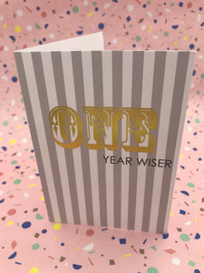 A stylish striped card with the words one year wiser written on the front