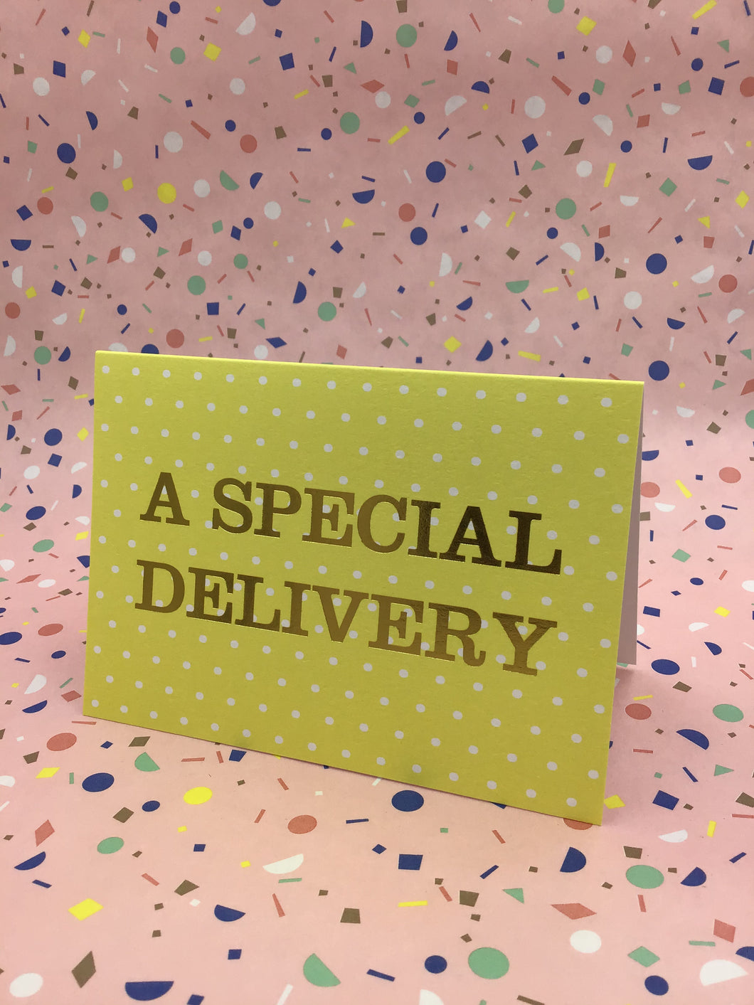 A lemon coloured card with gold spots and gold words