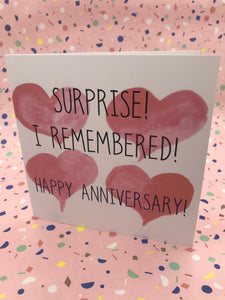 A card with love hearts and the words surprise I remembered - happy anniversary