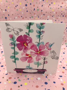A floral card with pink flowers and black and white butterflies