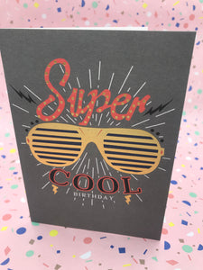 A grey card with gold sunglasses embossed