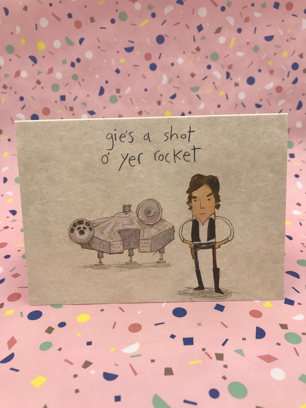 An illustrated card featuring a drawing of Han Solo and space ship