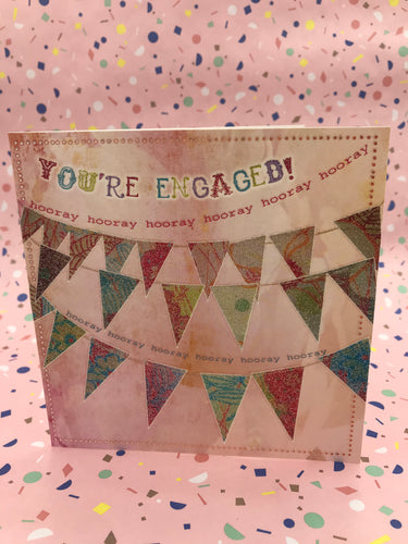 A pink card with glittery illustrated bunting over it