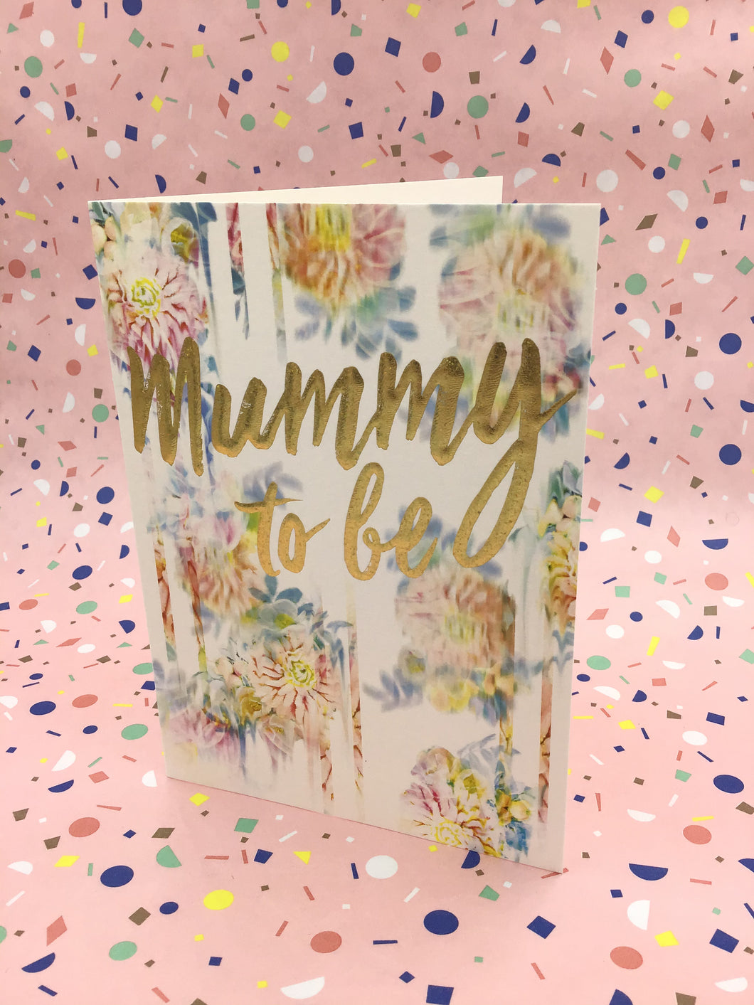 A floral pastel coloured card with gold writing