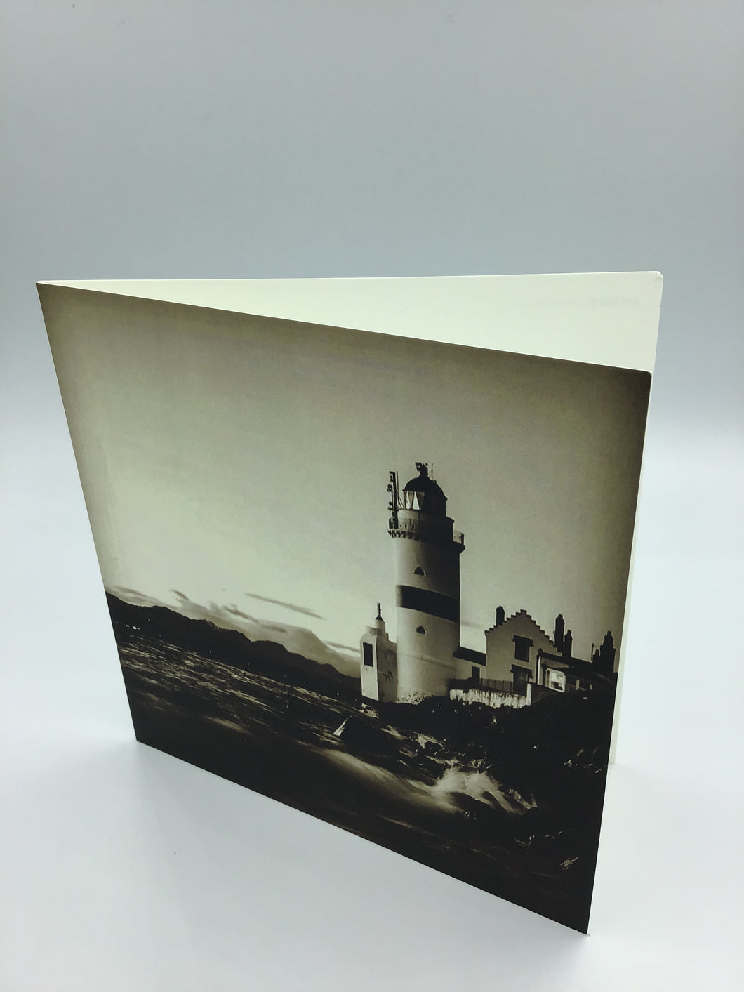 A sepia toned vintage style image of Cloch Lighthouse Gourock showing crashing waves on the shore