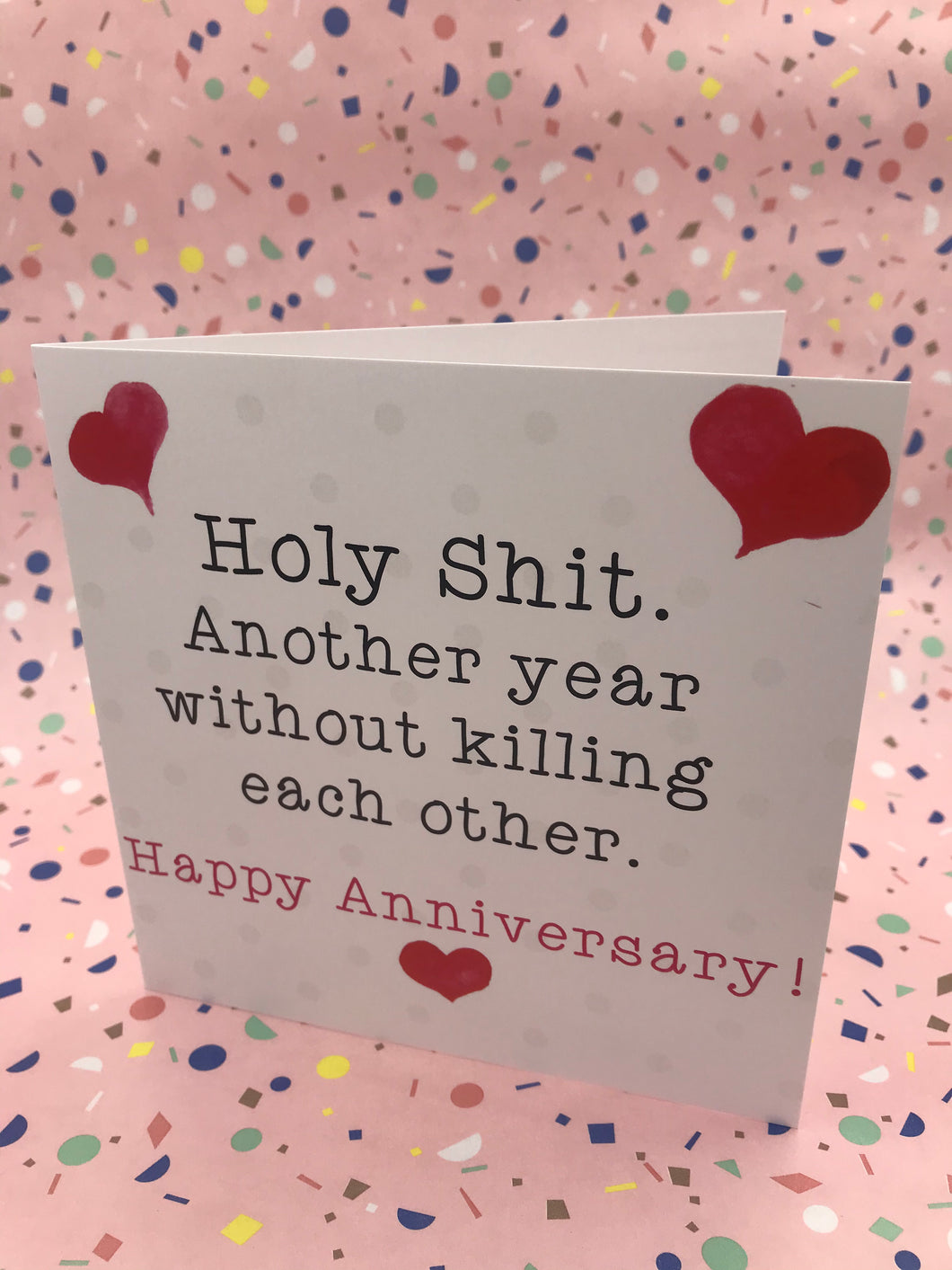 An illustrated card with love hearts and the words holy shit another year without killing each other
