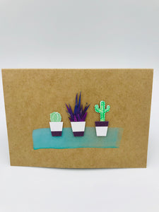 A handmade card featuring three cactuses