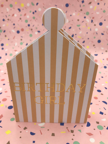 A pink and white striped card which becomes a crown to wear