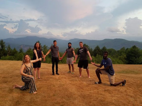 6 members of the Compt team stand and kneel in a field with clouds overhead in front of a beautiful forested mountain range.