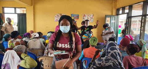 Entrepreneur Samirah Maison wearing mask and face shield in a classroom full of women.