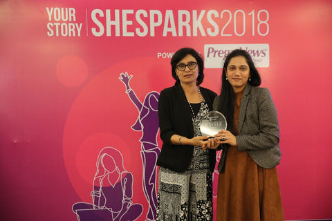 two women holding an award in front of a red photo backdrop at shesparks conference 2018.