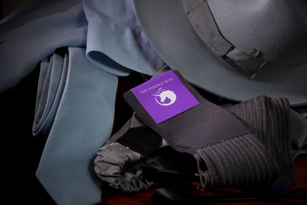 Elegance, The Purple seal dress socks new article. Image showing elegant garments: fedora hat, suspenders, necktie, light blue shirt, and The Purple Seal grey vanisee dress socks.