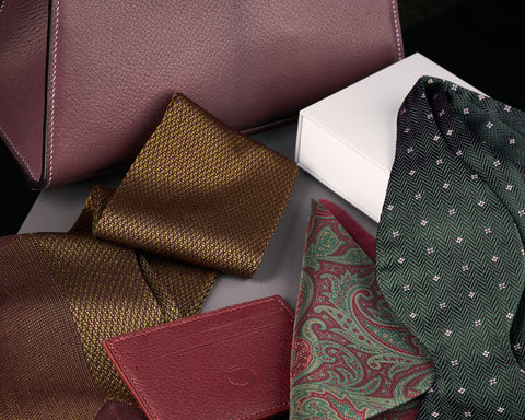 Selection of The Purple Seal products: leather handbag and cardholder, cotton and silk dress socks, silk pocket square and bowtie.