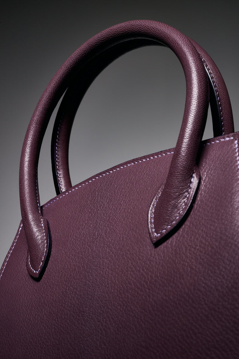 Plum purple goat leather handbag, handmade to order in the UK with top quality leather from France, Detail of rolled leather handles. The Purple Seal