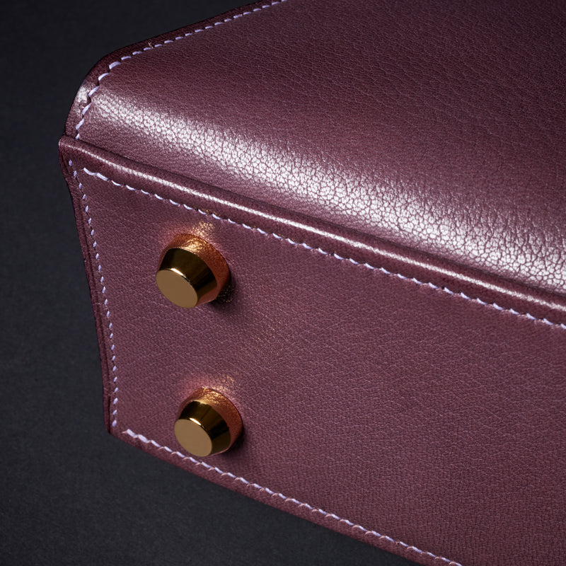 Plum purple goat leather handbag, handmade to order in the UK with top quality leather from France, Close up of solid brass gold feet. The Purple Seal