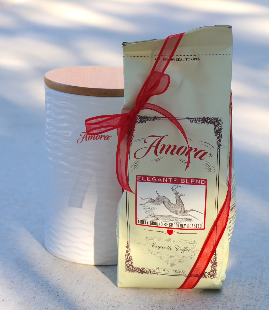 Image of bag of Amora coffee wrapped in red ribbon, next to an Amora coffee bean container