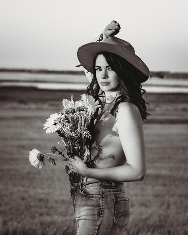 Image of article author Kelsey Fay pictured in a field holding flowers and wearing a hat