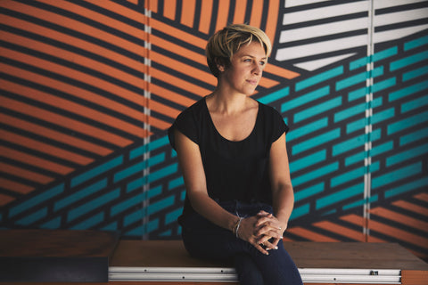Image of Amy Kubik seated on swing in front of mural; photo credit Tom Kubik