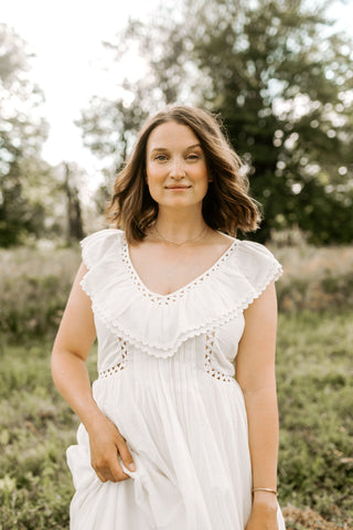 Image shows the author, Carley Schweet, wearing a white dress in a meadow. Image courtesy of Carley Schweet.