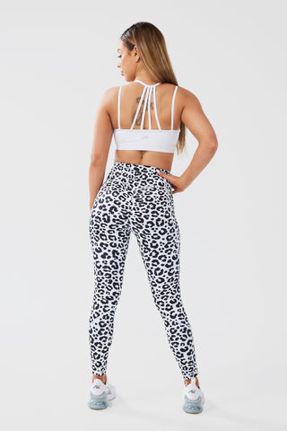 Girl posing hand on hip looking to side wearing luxe scrunch bum leggings in leopard print and white classic crop top