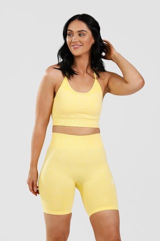 Girl wearing yellow calypso seamless shorts and sports bra front