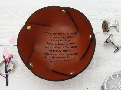 Leather coin tray with song lyrics shown with ring, cufflinks and watch