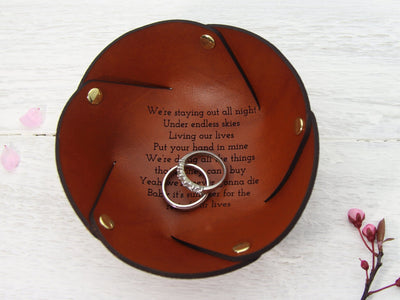 Leather ring dish with song lyrics shown with wedding rings