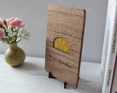 Wood card with yellow wool sunshine on wood stand on shelf