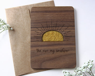 Wood card with wool sunshine displayed with flowers