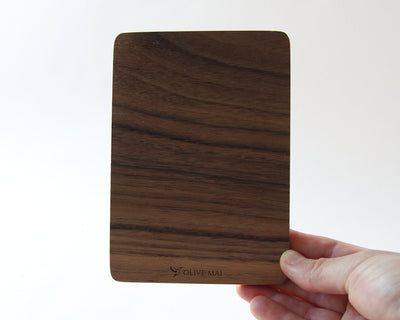 Holding walnut wood card, back view with Olive Mai logo engraved