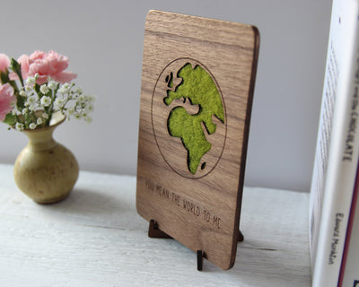 Wood card with world image and wool detailing on wood stand
