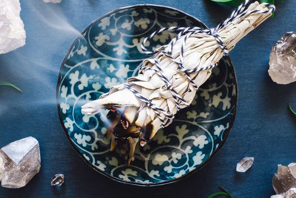 White sage cleansing bundle burning on blue & white dish