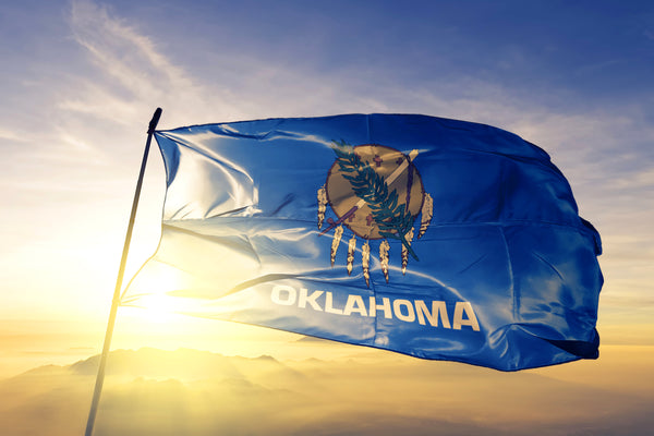 Oklahoma Flag in front of sunset