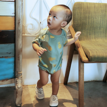 Load image into Gallery viewer, baby onesie with shimmer gold pineapple print in unique blue green teal seafoam colour. material is cotton spandex