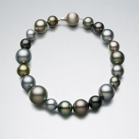 A BUNDA 'Strand' bracelet of Tahitian Pearls, round to semi - round in shape; green, peacock and platinum in colour, with clear skin and excellent lustre. Bracelet meausres 19cm long and is strung and knotted with an 18ct white gold ball clasp.  Dimensions of Pearls: 7.00 - 13.00mm  Weight of bracelet: 28.68 grams