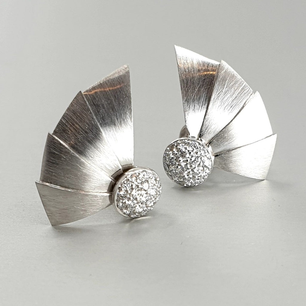 A pair of BUNDA 'Apus' small fan earrings in 18ct white gold. Each earring has a dome at the centre, pave set with round brilliant diamonds. Fittings are post and butterfly.  Characteristics of Round Brilliant Diamonds: 38 = 0.30ct, F Colour, VS Clarity  Total Weight = 3.66 grams