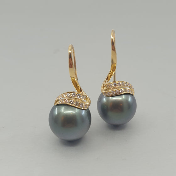 A pair of BUNDA Double 'Lyra' Cultured Tahitian Pearl Earrings in 18ct Yellow Gold. Each earring is set with a Tahitian Pearl, round in shape, dark green in colour, with clear skin and excellent lustre. The pearls are suspended from double 'Lyra' settings, threadset with round brilliant diamonds.  Characteristics of Green Tahitian Cultured Pearls; 2 x 15.0 - 15.10mm.  Characteristics of Additional Round Brilliant Cut Diamonds: 40 = 0.40ct, F colour, VS Clarity  Total weight: 15.38 grams.