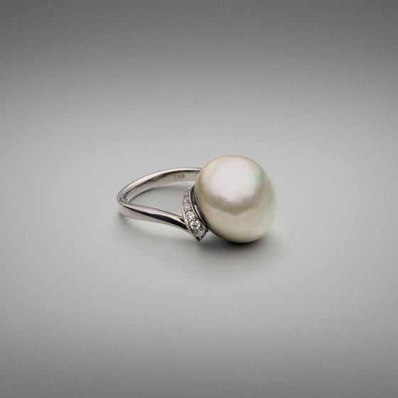 A BUNDA 'Lyra' Cultured Tahitian Pearl and Diamond ring made in 18 carat white gold, set with a button shaped pearl of clean skin and excellent lustre, platinum in colour with green tones. Round brilliant diamonds are thread-set in ribbon style setting beneath the pearl swirling to a plain shank in 18ct white gold.  Dimensions of pearl: 15.40mm  Weight of diamonds: 20 =0.38ct, F Colour, VS Clarity  Total weight of Ring: 9.46g