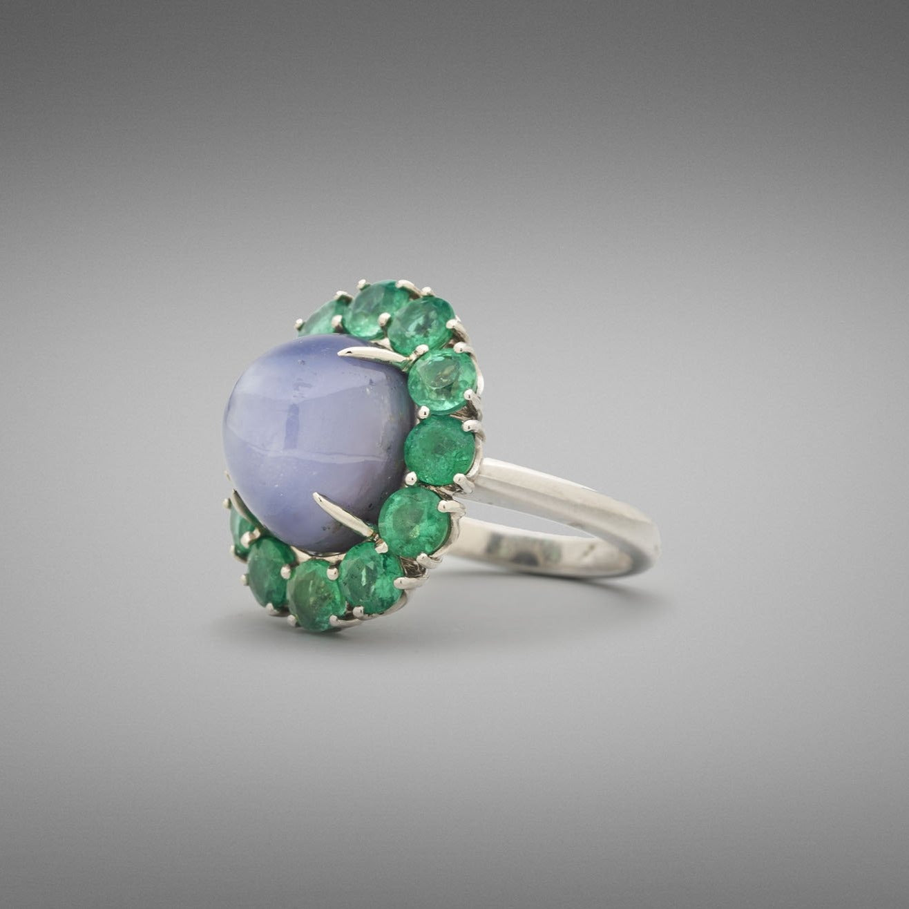 A BUNDA 'Cluster' ring made in platinum, centre set with a high domed blue star sapphire in a flour claw platinum setting. The centre stone is surrounded by a cluster of round brilliant cut emeralds in four claw settings.  Characteristics of Star Sapphire: 1 = 18.15ct  Characteristics of Emeralds: 12 = 3.35cts  Ring is stamped 'BUNDA' Total weight: 14.70 grams