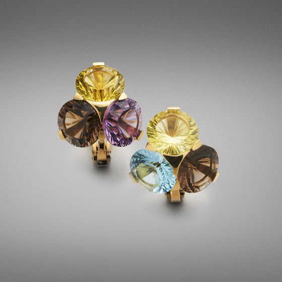 A pair of BUNDA 'Krest' multi gemstone earrings in 18ct yellow gold. One earring is set with lemon quartz, blue topaz and smoky quartz; while the other earring is set with lemon quartz, amethyst and smoky quartz; all in 18ct yellow gold 'Krest' claw settings. Each earring is fitted with a post and a large Omega clip.