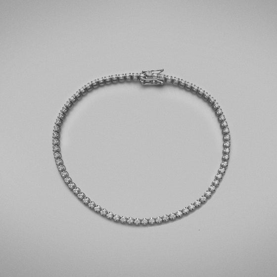 A BUNDA 'Tennis' bracelet in 18ct white gold. The bracelet is set with round brilliant diamonds in castle claw settings. Bracelet is stamped 'BUNDA'.  Characteristics of Round Brilliant Cut Diamonds: 87 = .69ct, F colour, VS Clarity  Total weight of bracelet: 5.19 grams