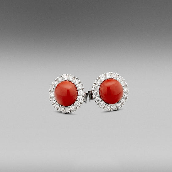 A pair of BUNDA 'Valentin' Precious Coral Earrings in Platinum. Each earring is set with a round cabochon of natural precious coral with castle-set round brilliant diamonds to the head.  Fittings are post and butterfly in platinum.   Characteristics of Red Cabochon cut Corals: 2 = 9.76ct.  Characteristics of Additional Round Brilliant Cut Diamonds: 32 = .83ct, F colour, VS Clarity  Total weight: 6.29 grams.