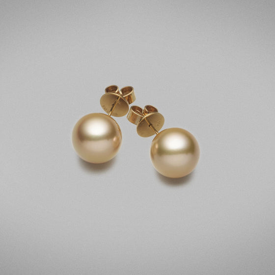 A pair of BUNDA Cultured South Sea pearl stud earrings in 18 carat yellow gold, set with round shaped pearls of clean skin and excellent lustre.  The pearls are an intense deep golden colour and measure approximately 12.90mm.  Fittings are post and butterfly.