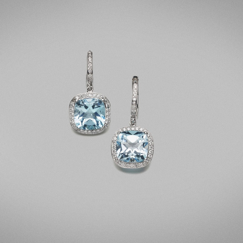 Each earring is set with a 2.64ct cushion cut sky blue topaz and is surrounded with a thread-set halo of round brilliant diamonds in platinum. The earrings have French hook and clip fittings. The hooks are thread-set with round brilliant diamonds in 18ct white gold.   Characteristics of topaz: 2 = 5.28cts  Characteristics of diamonds: 72 = 0.30cts, F Colour, VS Clarity  Total weight = 5.57 grams