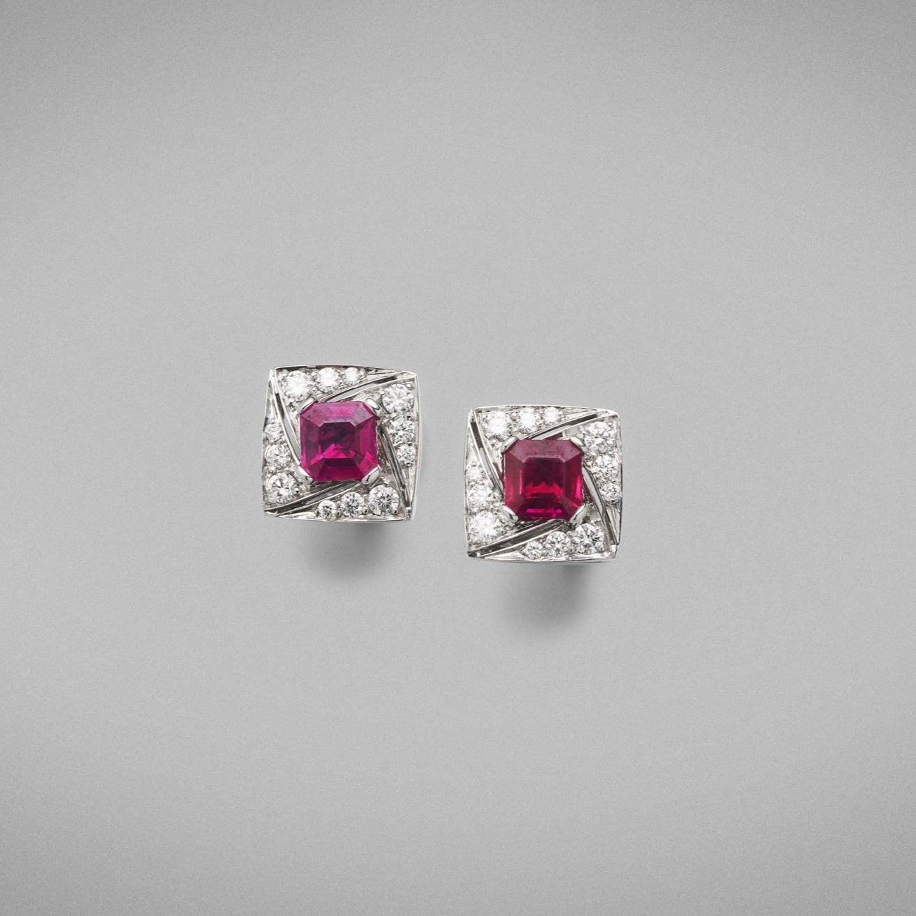 A pair of BUNDA 'Arya' Ruby and earrings in 18 carat white gold, featuring a pair of Asscher cut rubies, claw set to the centre and surrounded with thread-set round brilliant cut diamonds, with a post and butterfly fitting.  Characteristics of Ruby: 2 = 1.51ct.  Provenance: Burma (Myanmar)  Characteristics of diamonds: 24 = 0.36ct, F colour, VS clarity.