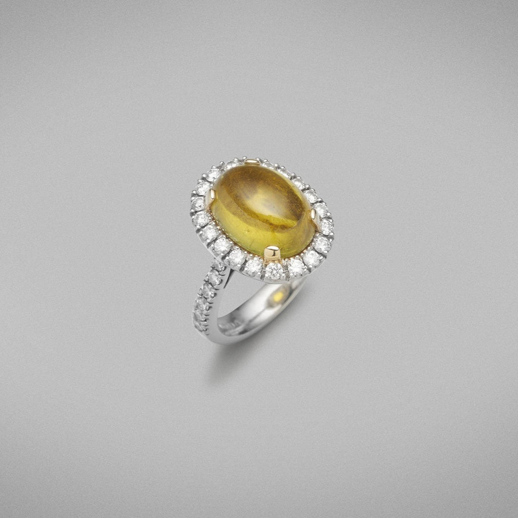 A BUNDA 'Valentin' Tourmaline and diamond ring in platinum and 18ct yellow gold, featuring a cabochon cut Tourmaline, surrounded with castle set round brilliant cut diamonds to the head and shoulders.  Weight of Tourmaline: 1 = 6.64ct  Characteristics of additional diamonds: 32 = 1.01ct, F colour, VS clarity.  Total weight of Ring: 12.28 grams.