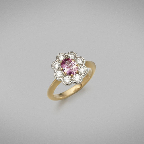 The ring is set with a 0.86ct pink spinel from Tanzania in an eight claw 18ct yellow gold setting. The centre stone is framed with eight round brilliant diamonds in platinum settings.  Total Diamond Weight: 8 x diamonds = 0.82ct. F Colour, VS Clarity  Ring weighs 6.18 grams