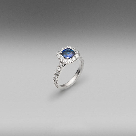 'Valentin' Sapphire and diamond ring in 18 carat white gold, featuring a cushion cut Ceylon Sapphire, weighing 1.17ct, surrounded with castle set round brilliant cut diamonds set in the halo and on the shoulders.  Total diamond weight = 1.16ct.