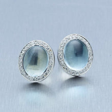 A pair of BUNDA 'Corvus' aquamarine earrings in 18 carat white gold, featuring a pair of cabochon cut aquamarines, bezel set and surrounded with threadset, round brilliant cut diamonds, fitted with a post and butterfly fitting.  Weight of aquamarine: 2 = 5.63ct.  Characteristics of diamonds: 52 = 0.23ct, F colour, VS clarity.